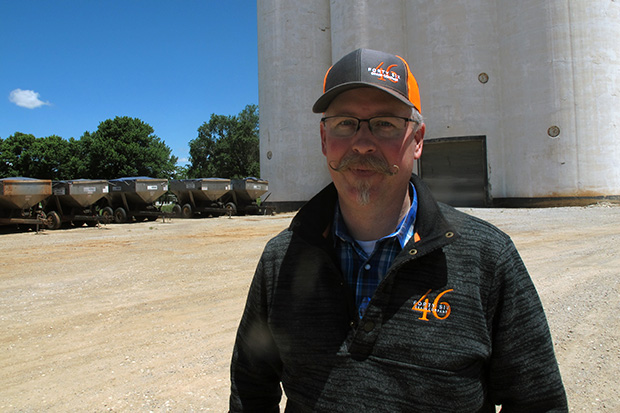 J.D. Drennan, senior agronomist for 46 Grain Company, stands in front of the grain elevator at Farmers' Elevator Company in Ames, Oklahoma.