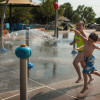 Olivia and Carter Kempen playing on a splash pad in Edmond, Okla.