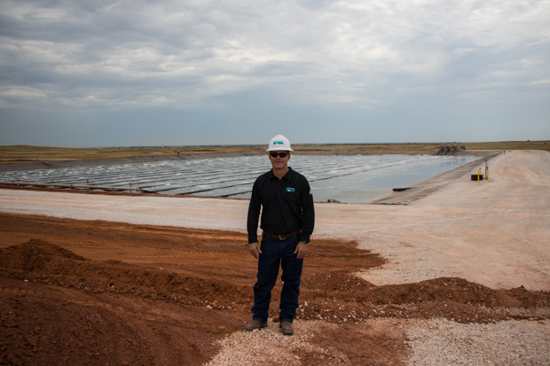 Reed Durfey, a water and technical services manager with Newfield, stands in front of the containment pond at the Barton Water Recycling Facility.