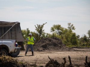 A worker brushes dusty mine waste off a truck before it exits the contaminated site.