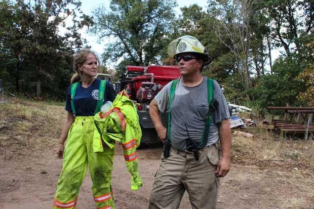Volunteer firefighters Christie Smith and David Thompson cool down after extinguishing a hotspot that flared east of Noble, Okla., in 2012. Scientists expect the risk of wildfire to increase as climate change-fueled droughts occur more frequently and last longer.