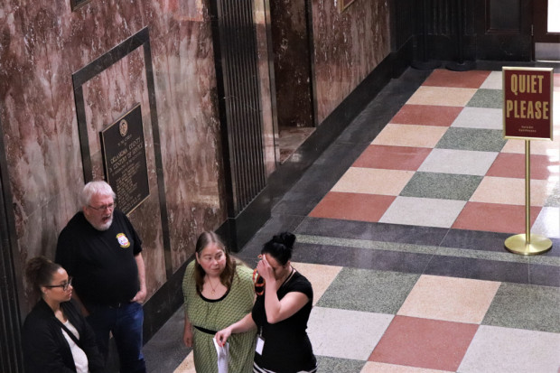 A group of people stand outside a courtroom at the Oklahoma County courthouse.