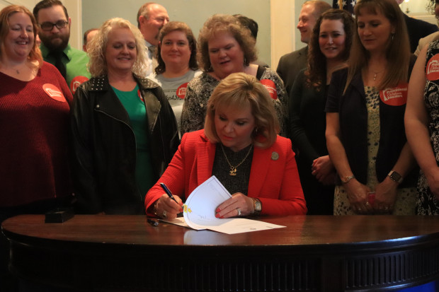 Flanked by teachers from the Professional Oklahoma Educators organization, Governor Mary Fallin signs a new teacher pay raise into law. March 29, 2018. .