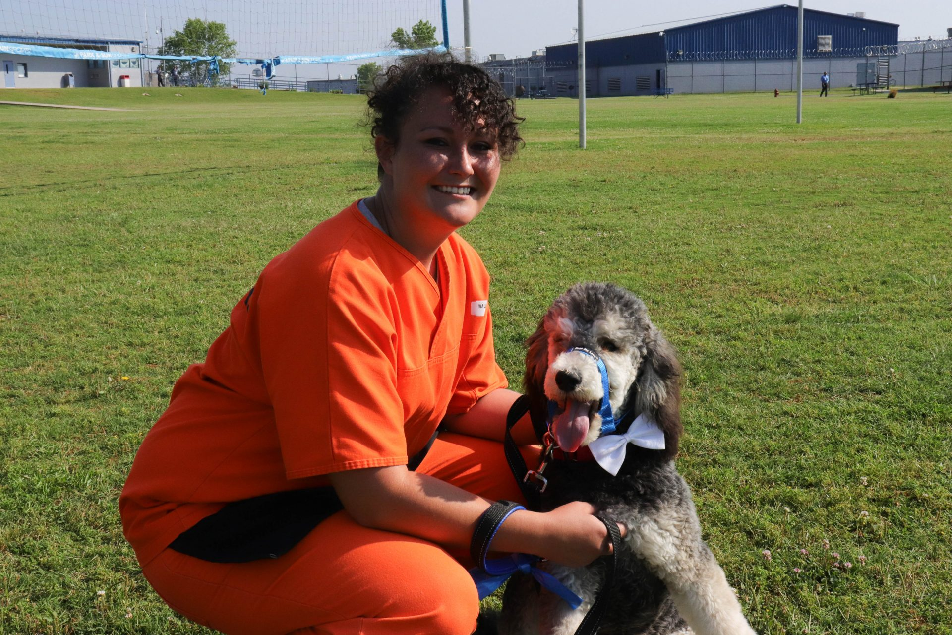 Inmate Lacey Wallace poses with her dog trainee, McAlester, on the yard in Mabel Bassett Correctional Center.