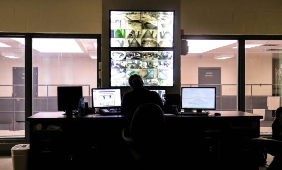 A Canadian County employee keeps watch in the control room of the county jail.