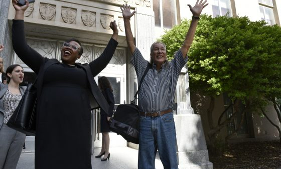Innocence Project attorney Karen Thompson and Johnny Tallbear raise their hands in celebration after Tallbear's release