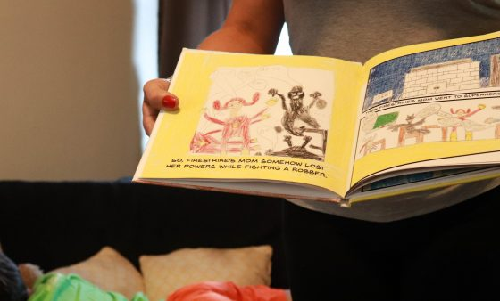 Alexis Stephens holds the comic book her son created while her son sleeps on a couch in the background.