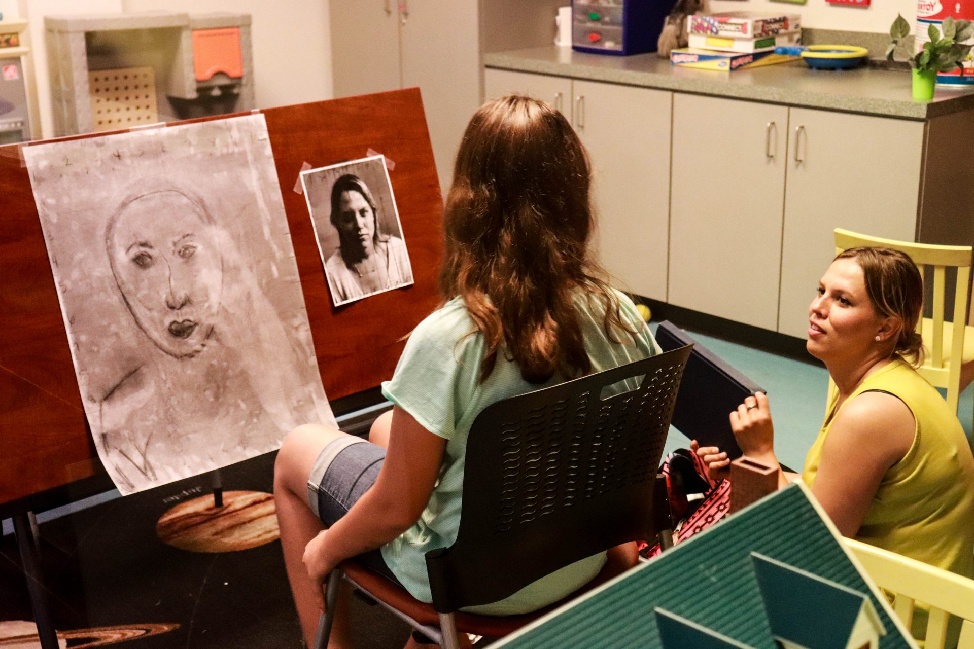 Sarah Sinkinson and her daughter collaborate on a charcoal drawing in a visitation room at Women in Recovery.