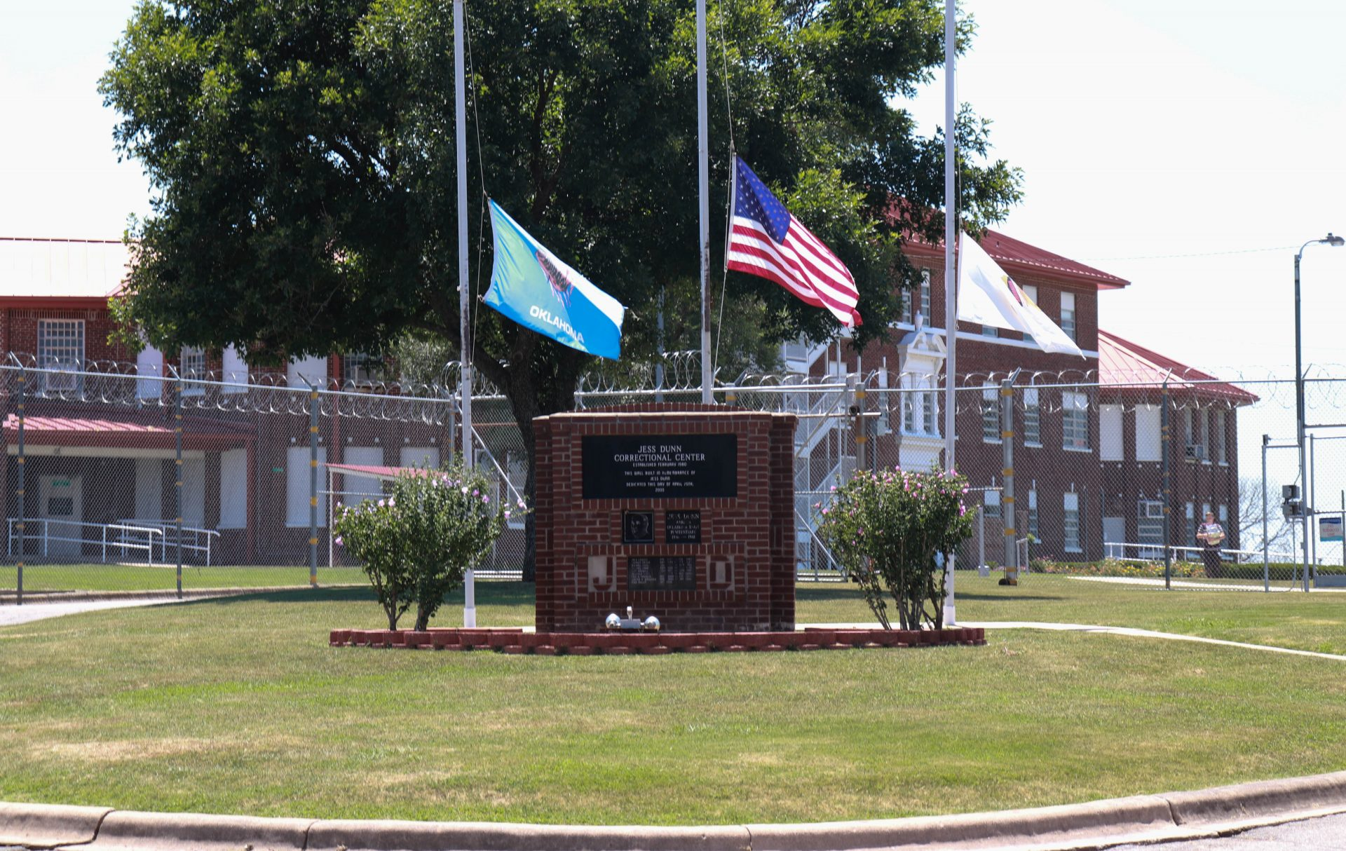 Flag Poles and a sign identifying Jess Dunn Correctional Center inside the prison's grounds.