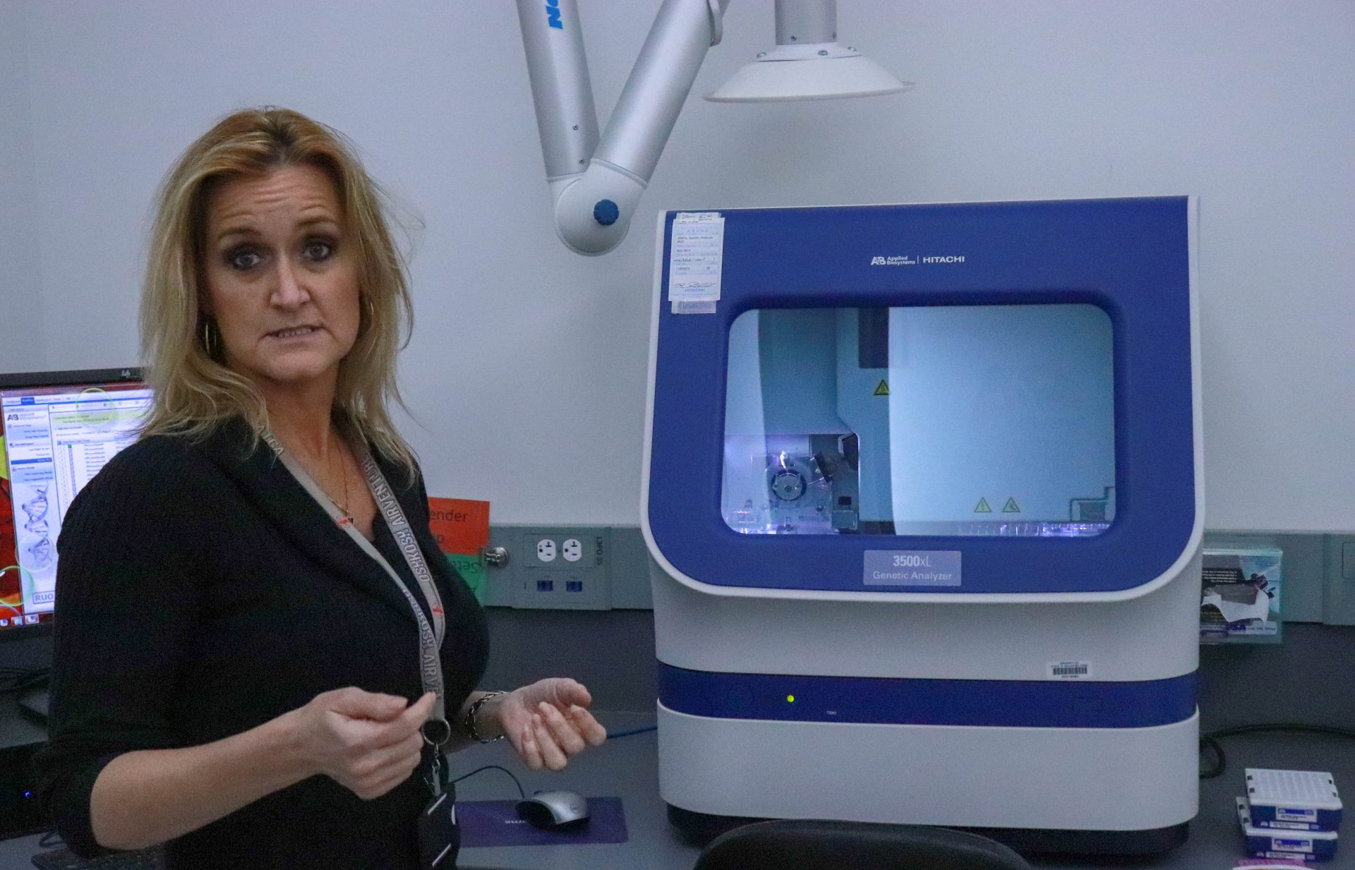 Andrea Fielding stands in an OSBI lab next to a machine used to analyze DNA.