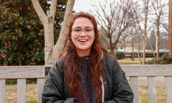 Lauren Atkins sits on a bench on the University of Oklahoma's campus.