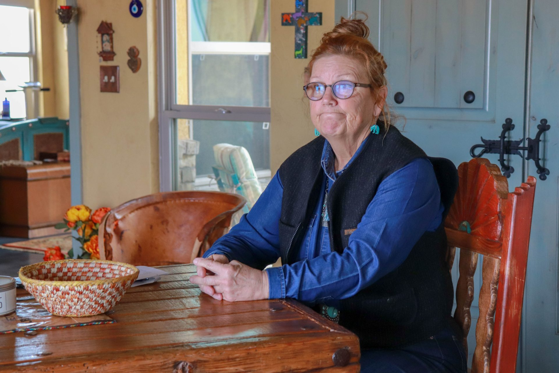 Terry Sue Barnett sits at a table inside her home.