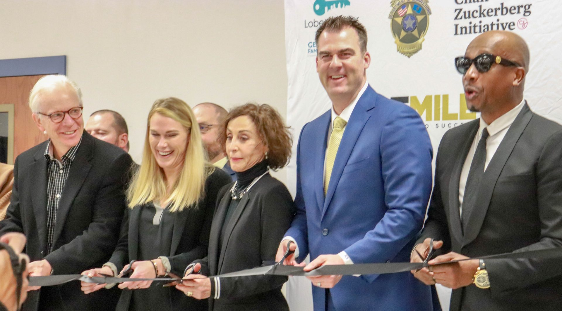 Gov. Kevin Stitt smiles while participating in a ribbon cutting ceremony.