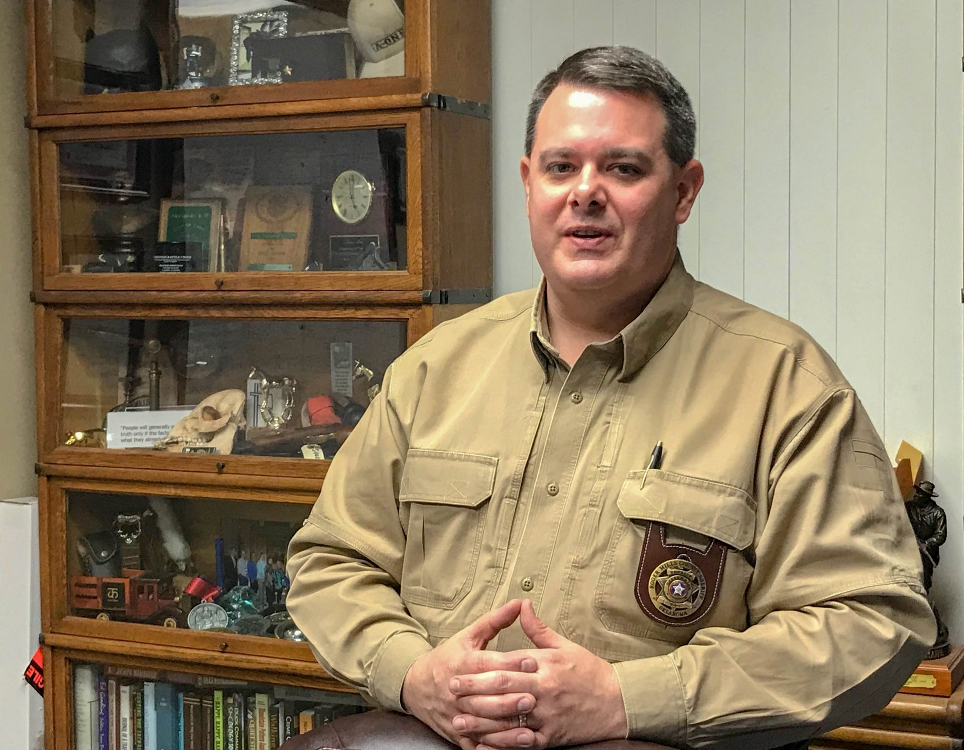 Sheriff Darren Atha stands behind his desk in front of a trophy case.