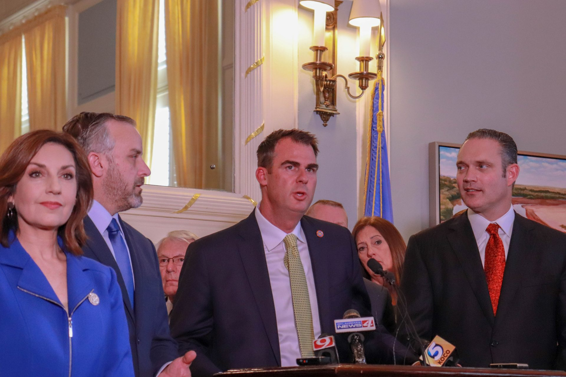 Gov. Kevin Stitt stands at a podium and announces a budget deal while flanked by legislative leaders.