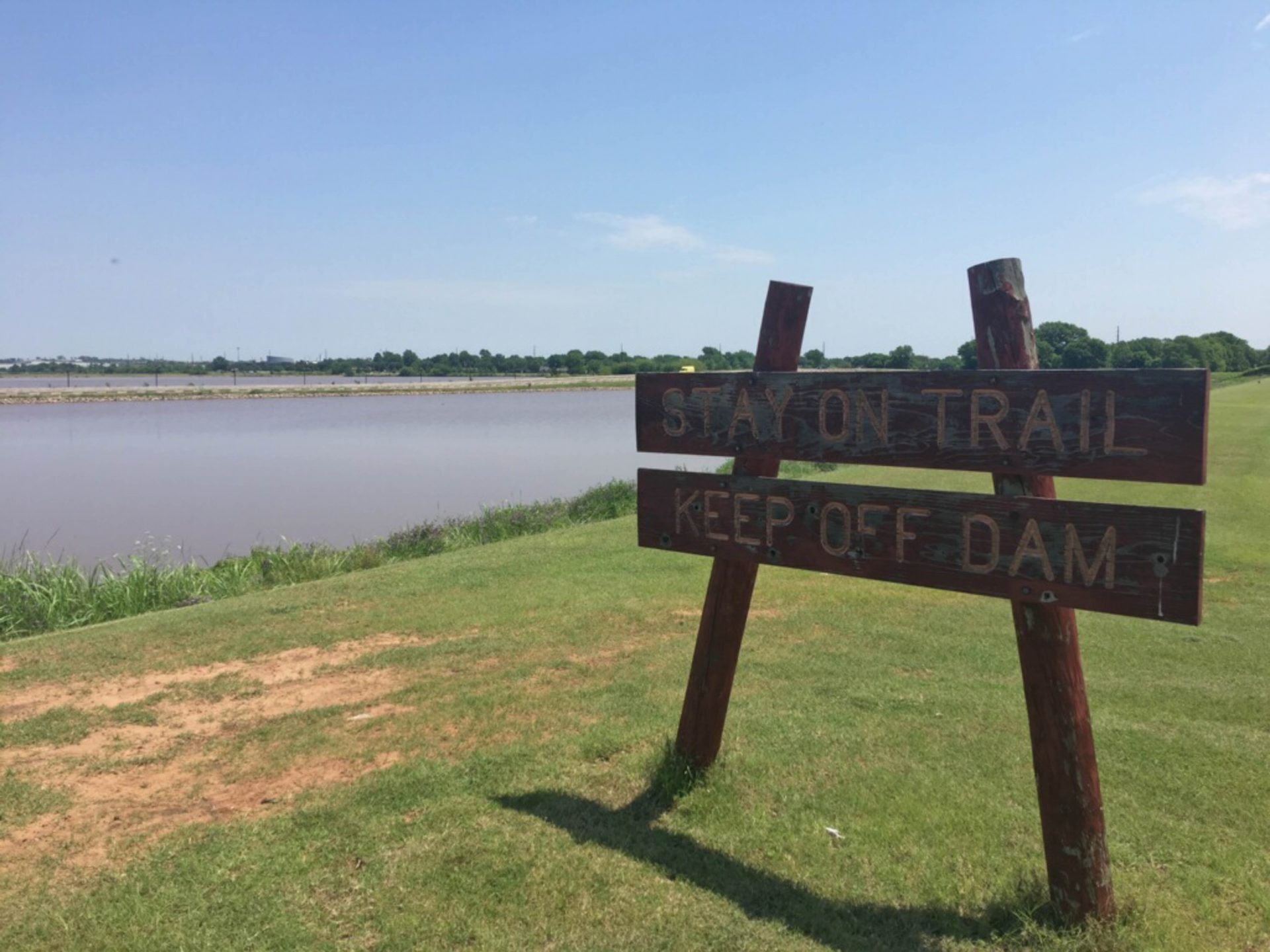 A warning sign posted on a slope in front of the Boomer Dam cautions people not to walk on the dam.