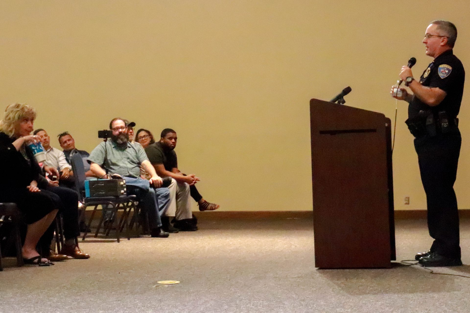 An Edmond police officer stands at a podium and answers audience questions inside an auditorium.
