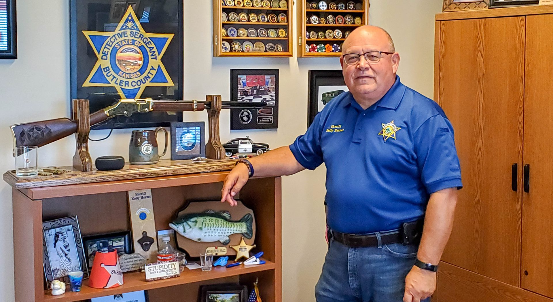 Sheriff Kelly Herzet stands next to a shelf in his office.