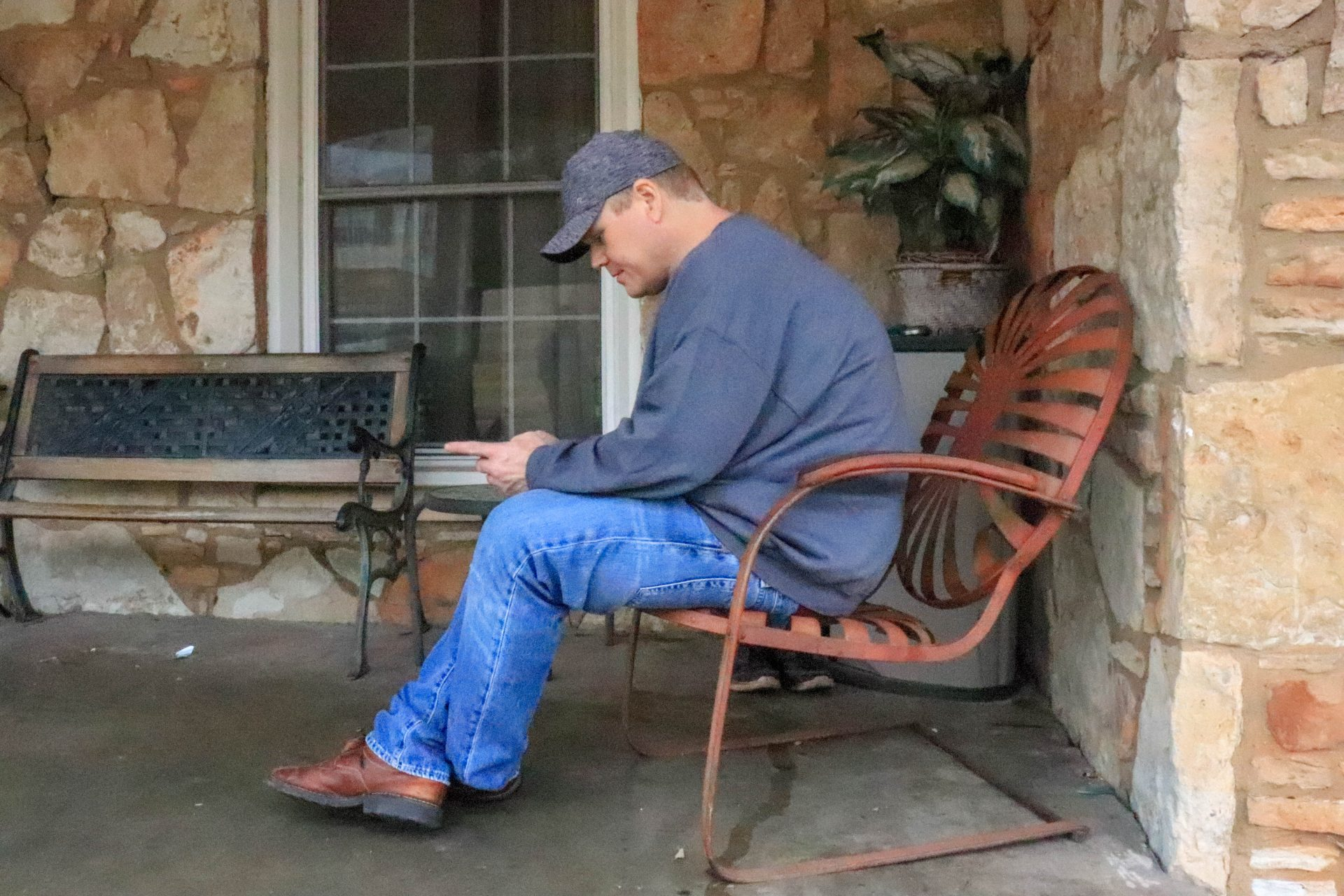 Warren Rawls sits on a bench in front of a stone house.