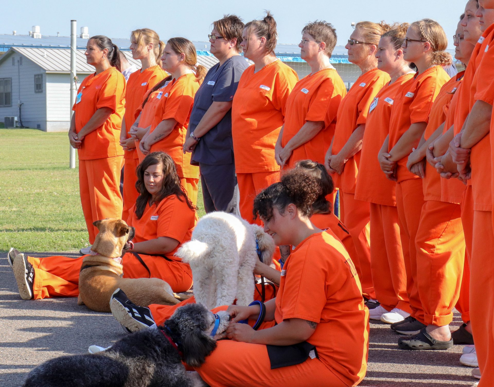 Women incarcerated at Mabel Bassett Correctional Center attend a ceremony commemorating a dog training program at the prison.