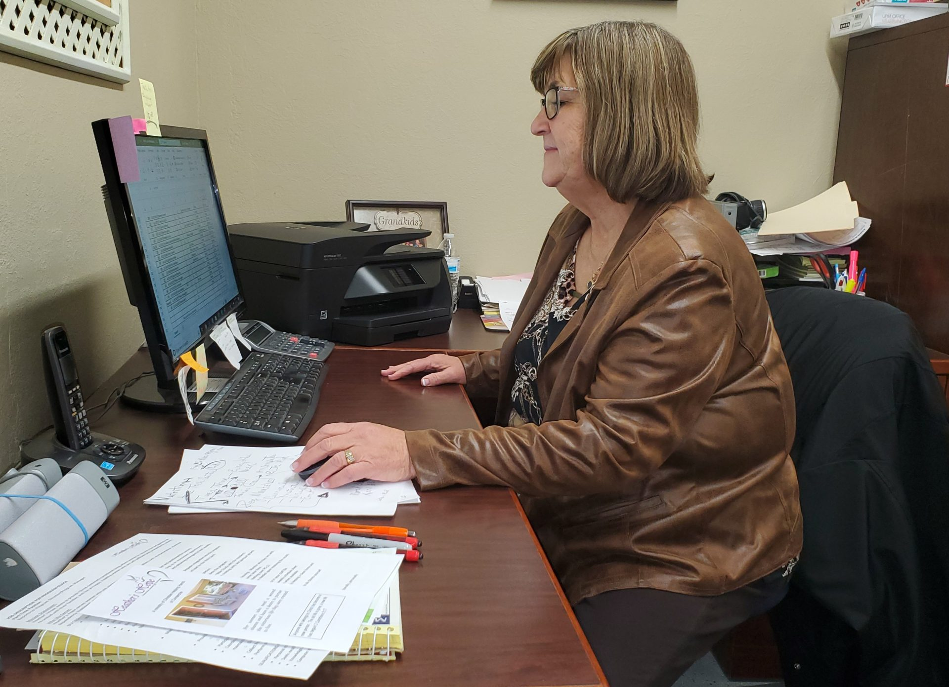 Pam Dobbins sits at her office desk in Comanche.
