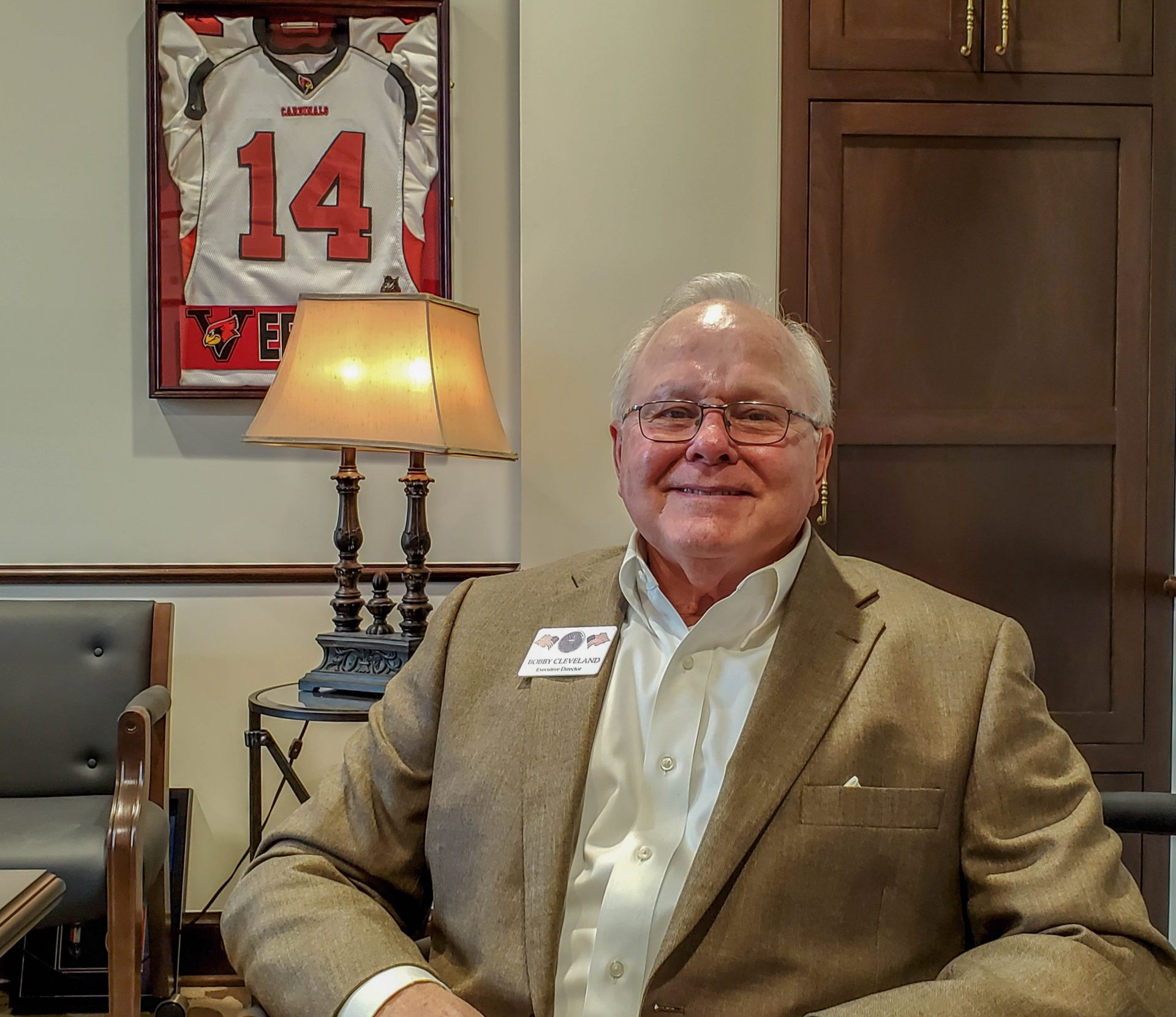 Bobby Cleveland sitting in an office at the state Capitol. A framed Arizona Cardinals jersey hangs behind him.