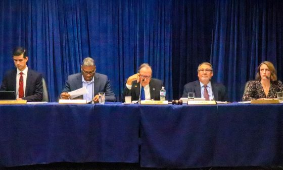 Oklahoma Pardon and Parole Board members sitting at a table draped with a blue table cloth with blue curtains in the background.