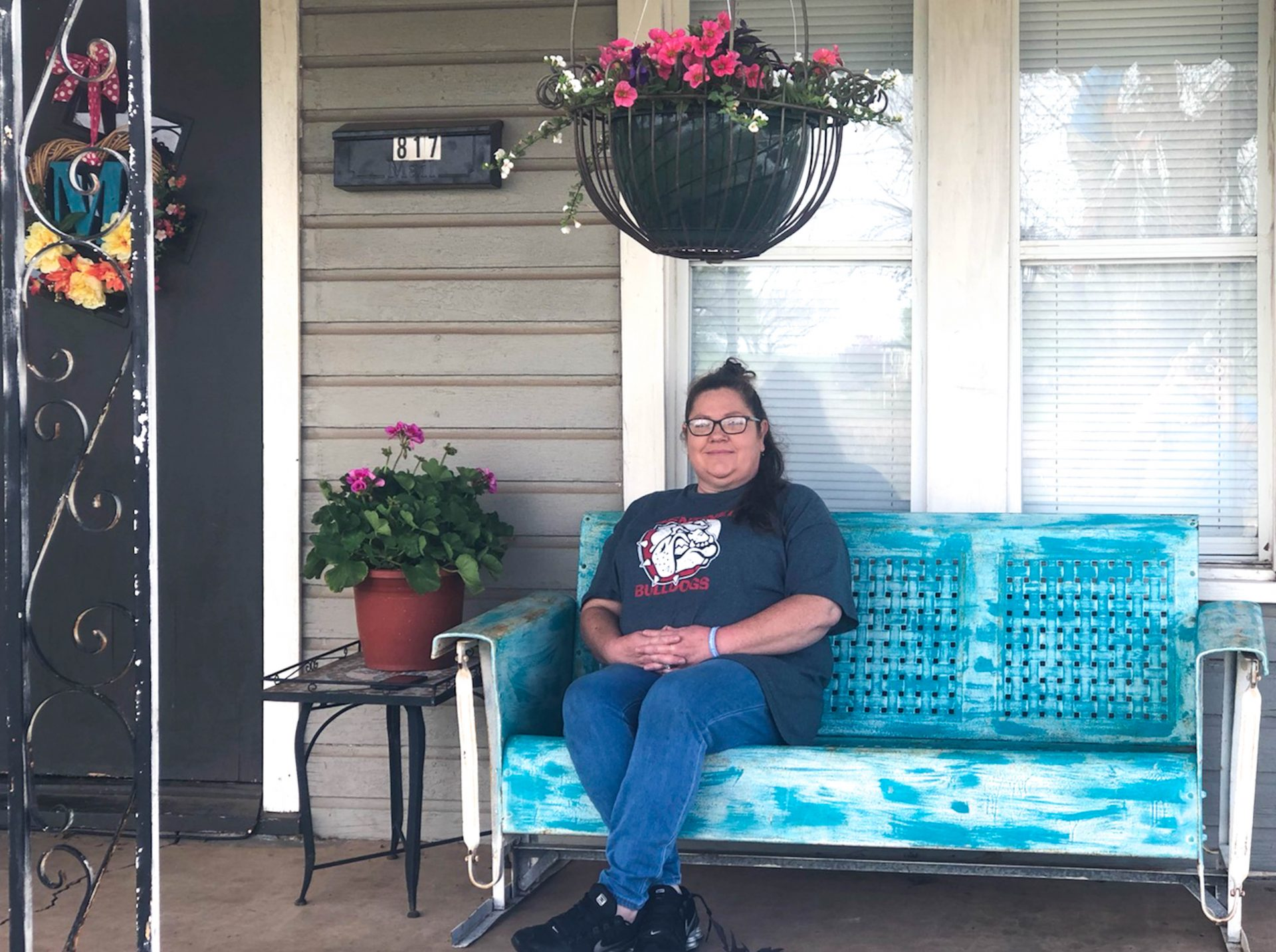 Sarah Morrow sitting on the porch of her house.
