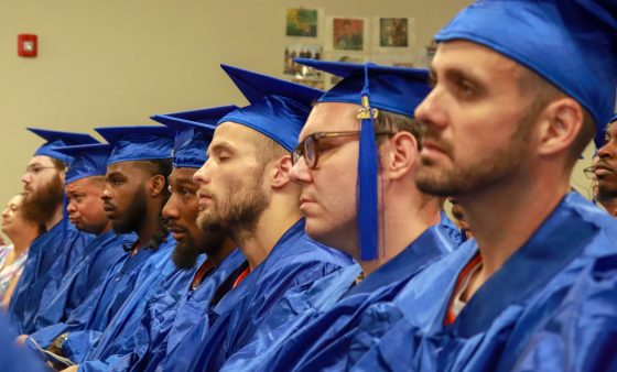 Prisoners in blue graduation gowns sit during graduation ceremony.