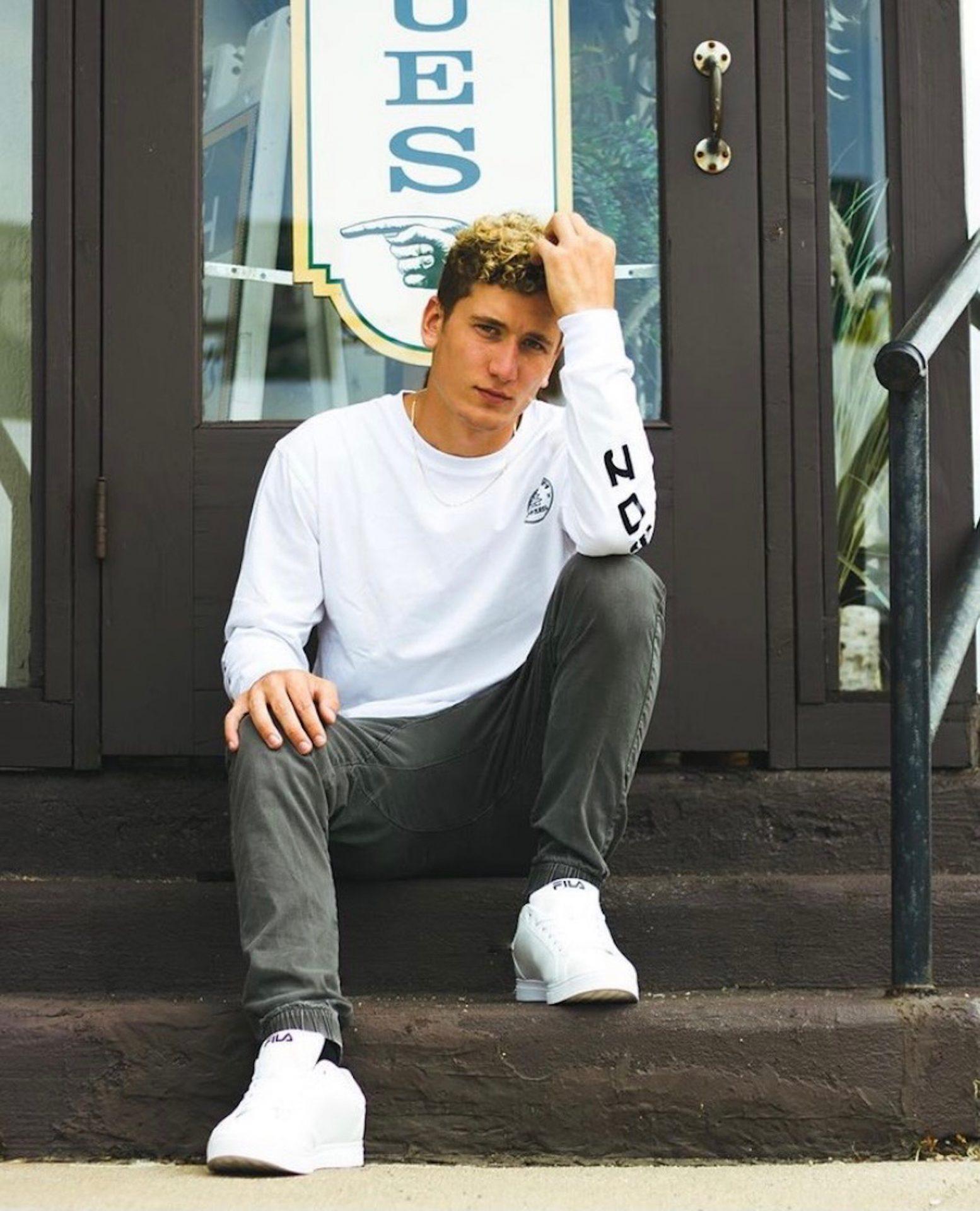 Jan Cervenka sitting on steps in front of a glass door.