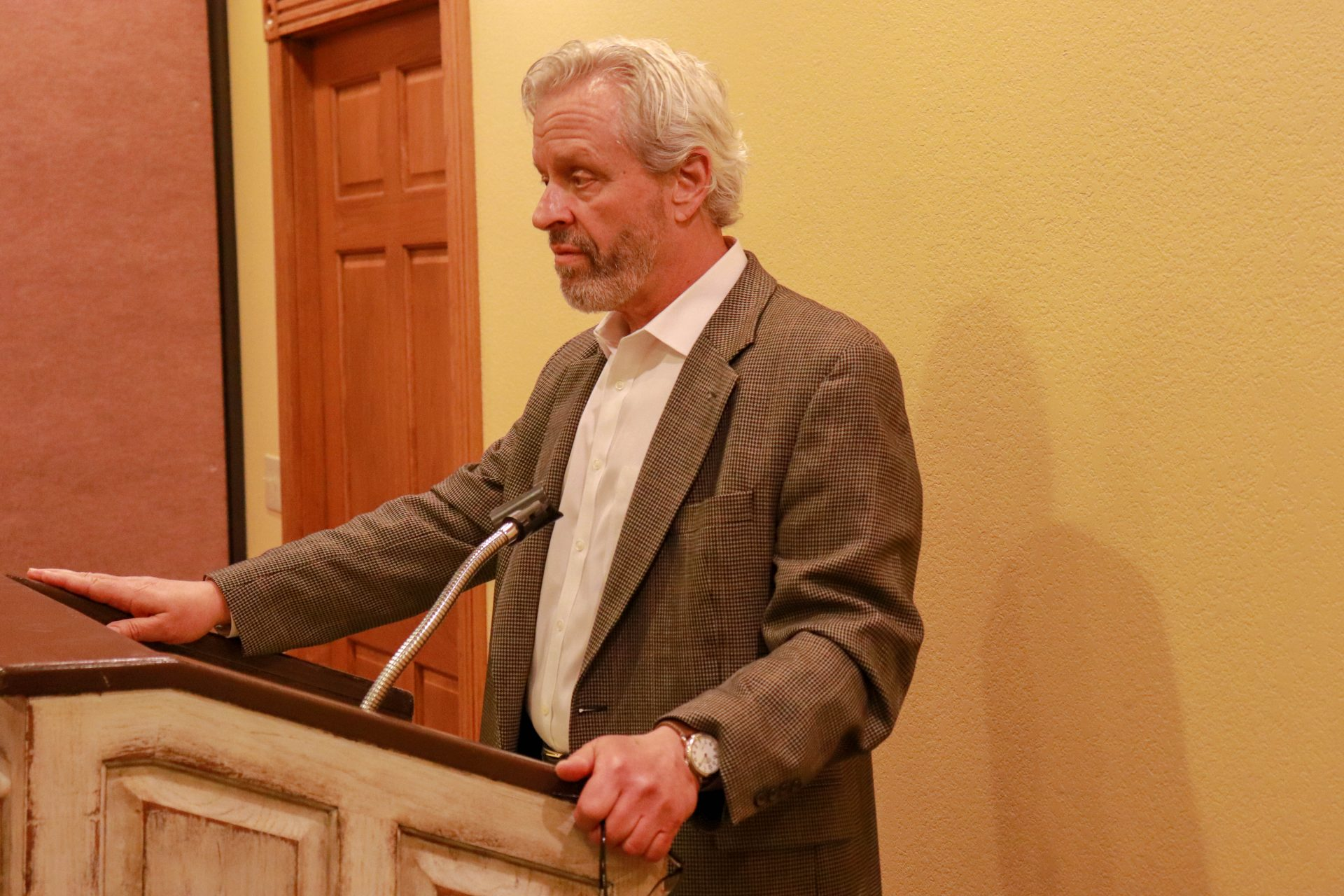 Don Knight stands at a wooden podium inside a private dining room in Pete's Place.