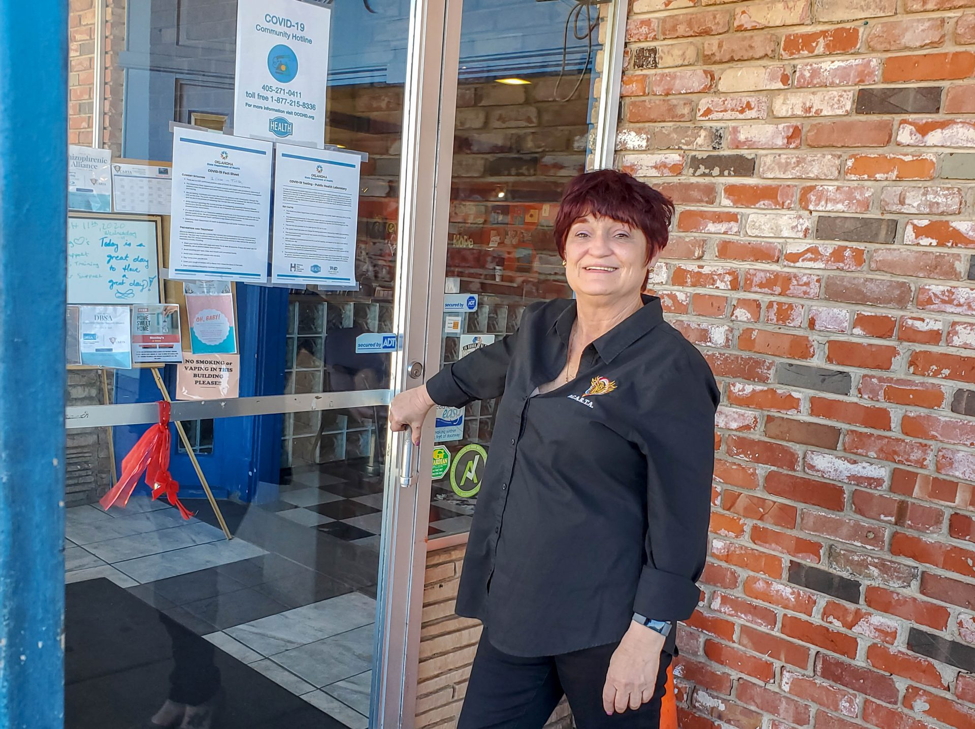 Donna Woods standing outside a glass paned door that leads into OCARTA.