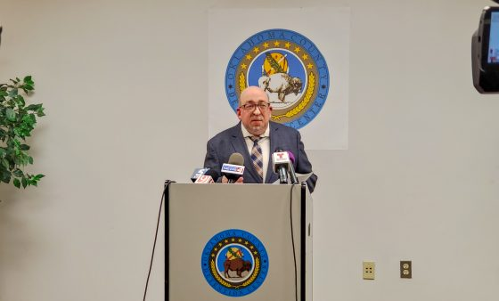 Timothy Tardibono is standing behind a podium with the Oklahoma County Detention Center's seal affixed to the front and the wall behind it. There is a partial view of a camera viewfinder to the right and a partial view of another camera's lens to the left.