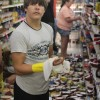 Brandon Bennington helps clean up after Tuesday's earthquake knocked food off supermarket shelves in Mineral, Va.