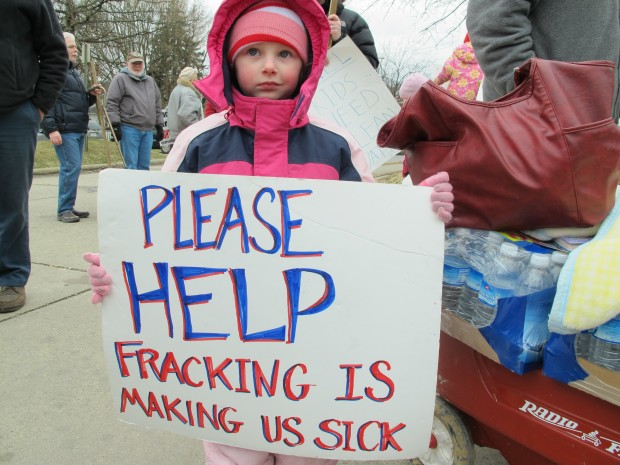 Skylar McEvoy holds up a sign at a rally in Butler, Pa. She and her family moved after they say fracking polluted their water. Her mother Kim says the DOH was no help.