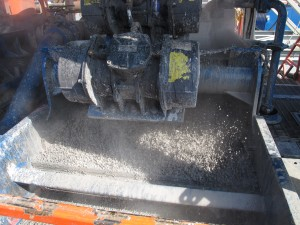 """The """"cuttings"""" - rock and dirt from deep underground - are churned up by a drill to be loaded into a dumpster at a well site in Susquehanna County, Pa."""