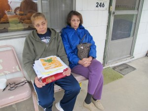 Jeanie Moten with her sister on their mother's porch in Rea, Pa. She holds a stack of medical records. The Motens say they received no help from DOH regarding their fracking health complaints. A case file released by the DOH through a Right-To-Know request confirmed that.