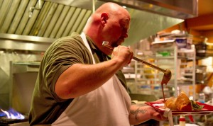 Summerhouse Grill chef pours a porter béchamel sauce over the pork sausage strudel.