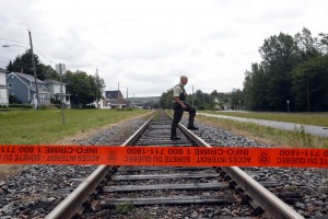 Quebec Provincial Policeman crosses the railway tracks inside the exclusion zone in the town of Lac Megantic, Quebec.  Hundreds of residents were evacuated from their homes when a runaway train loaded with crude oil exploded on July 6. Up to 50 people have either died or are still missing.