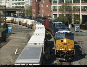 The CSX K040, an oil train bound for South Philadelphia, chugs past an intermodal train through Center City.