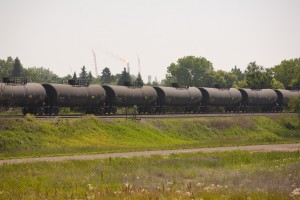 A train pulling a row of tank cars moves along the tracks near a Hess transfer facility near Tioga, North Dakota, U.S., on Thursday, July 11, 2013. There is a continued boom situation in the area due to the ability to extract oil from the Bakken Formation.