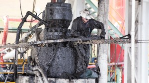 A drill worker covered in mud, shale, and drill cuttings seals off a well and cleans the blowout preventer at a Cabot Oil & Gas natural gas drill site in Kingsley, Pa.
