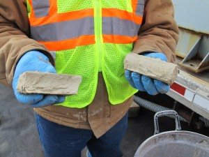 A worker breaks apart a brick of solid material left over from treating frack water. The solid material, which may contain radioactive elements, gets disposed of in landfills.