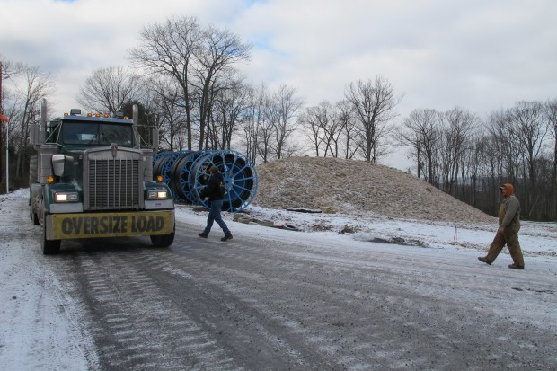 An oversize truck load of natural gas industry equipment moves slowly along an icy mountain road in the Tiadaghton state forest.