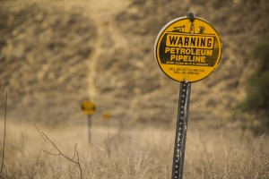 Signs mark a petroleum pipeline.