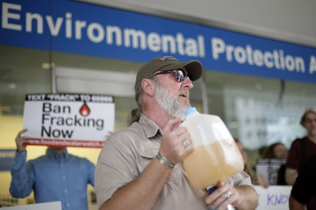 Ray Kemble of Dimock, displays a jug of what he identifies as his contaminated well water in this August 2013 file photo. The EPA included Dimock as a case study in its draft fracking report.