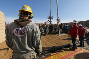 Workers keep an eye on well heads during a hydraulic fracturing operation at an Encana Corp. oil well, near Mead, Colo.