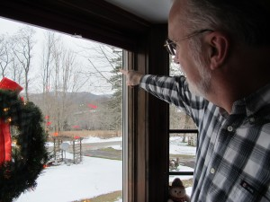 Chuck Winschuh points to a natural gas compressor station across the valley below his home in Dimock Township in Susquehanna County, Pa.