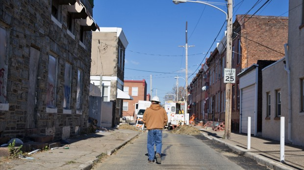 PGW area supervisor Carlos Rojas walks toward a work site where aging gas lines are being updated.  Philadelphia plans to replace 1,500 miles of cast-iron pipelines in the city over 88 years.