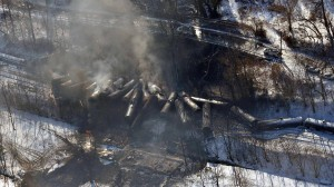 In this aerial photo made available by the Office of the Governor of West Virginia shows a derailed train in Mount Carbon, WV., Tuesday Feb. 17, 2015.  The train carrying crude oil derailed Monday night, causing a large fire that forced hundreds of people to evacuate their homes and temporarily shutting down water treatment facilities. (AP Photo/ Office of the Governor of West Virginia, Steven Wayne Rotsch)